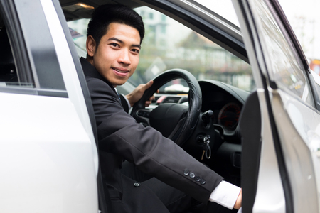 Young businessman open the door of his car. Business and car service.
