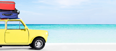 Vintage yellow car on the seaside beach with travel bags on the roof. Travel and Leisure trip in the summer. Stock Photo
