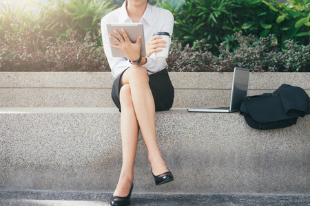Asian business woman ralaxing at park outside office. Business people working outdoors.