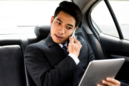 Busy businessman using mobile phone and tablet in car. Online Business and Mobile office concept.