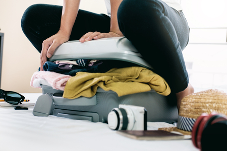 Preparation for vacation or travel. Packing his clothes and stuff into large opened suitcase that almost already full. Stock Photo