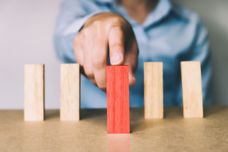 Business concept in choose idea person from many candidate and different. Close up hand pick one of red wood block from many wood block in row.
