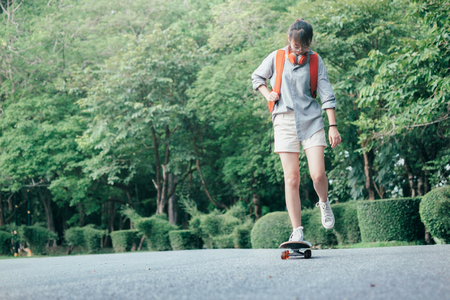 Young teen girl riding on longboard on the road. Extreme sports.