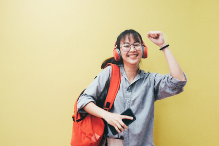 Teen lifestyle concept. Happy pretty hipster girl in earphones listening to music and dancing and holding mobile phone on bright yellow background.