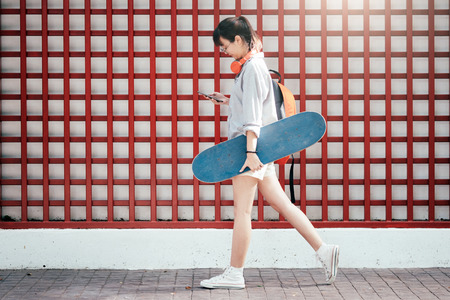 Young hipster asian girl walking and holding skateboard and using mobile phone to chating. Stock Photo