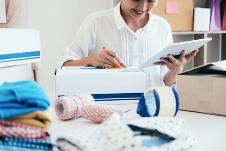 Young business start up online seller owner using computer for checking the customer orders from email or website and preparing packages for product office equipment.  Stock Photo
