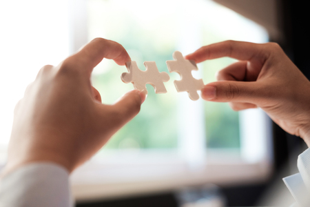 Businessman hand connecting jigsaw puzzle. Business solutions, success and strategy concept.
