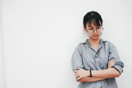 Portrait of thinking and angry and loanly young woman on white background. 写真素材