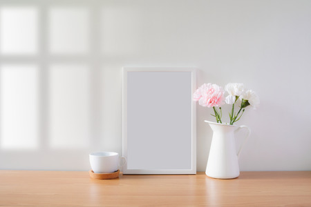Mock up protrait photo frame with flowers on table, home decoration.