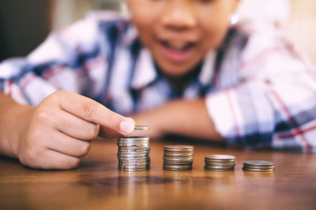 Saving money concept. Kid counting money and make coin stack. Reklamní fotografie