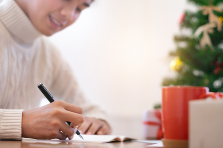 Christmas  concept.  Man wearing white sweater writing greeting cards. Archivio Fotografico