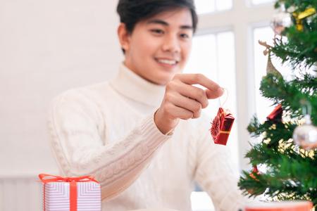 Hombre joven que adorna el árbol de navidad. Decoración navideña y año nuevo.