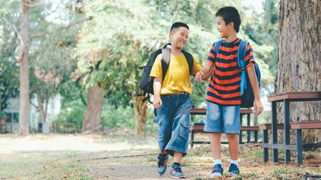 Back to school and education concept. Two boys of primary with school bags behind the back. Little first graders. Banco de Imagens