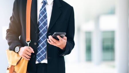 Young businessman on smartphone walking in street using app texting on smartphone.