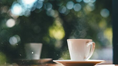 Coffee cup on the wooden table and green bokeh background in the morning sunrise. 写真素材