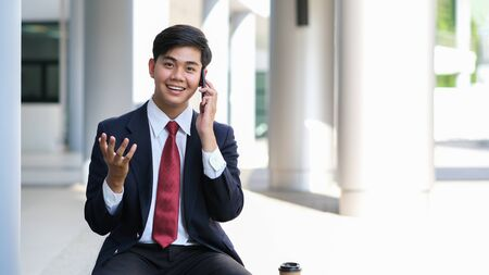 Young businessman in black suit speaking over mobile or smart phone with business partners. Business outdoors. Фото со стока
