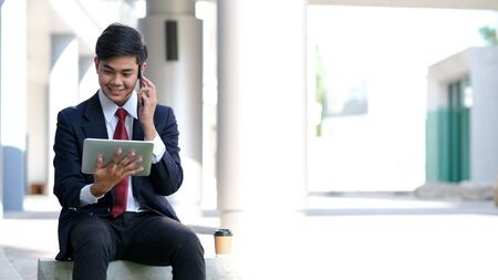 Young businessman in black suit speaking over mobile or smart phone with business partners. Business outdoors. Фото со стока - 136714306