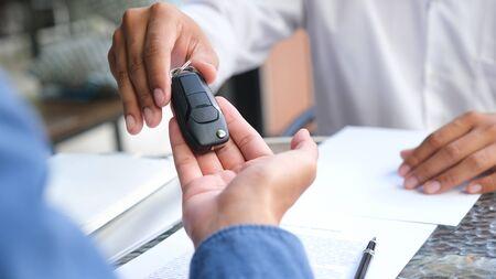 Bedrijfsconcept, autoverzekering, auto verkopen en kopen, autofinanciering, autosleutel voor autoverkoopovereenkomst. Nieuwe autobezitters nemen sleutels af van mannelijke verkopers. Stockfoto
