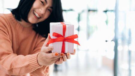 Closeup hands holding gift box of happy smiling young woman. Фото со стока - 137269999