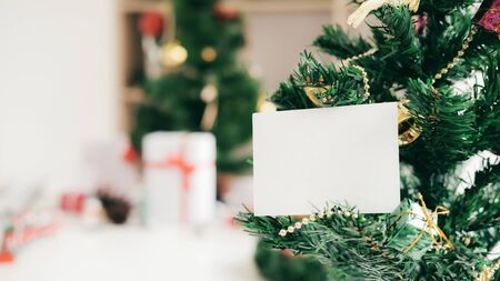 Empty white card on Christmas tree.  Holiday copyspace concept. Imagens