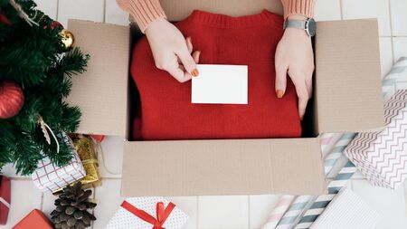 Woman prepare christmas and new year gift and put the card into box. Charistmas and New year and Birthday concept.