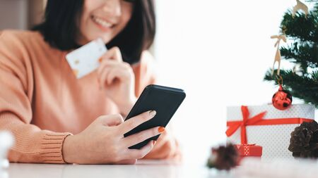 Young woman holding credit card and doing shopping online. New year, Christmas gift shopping. Фото со стока - 137270000