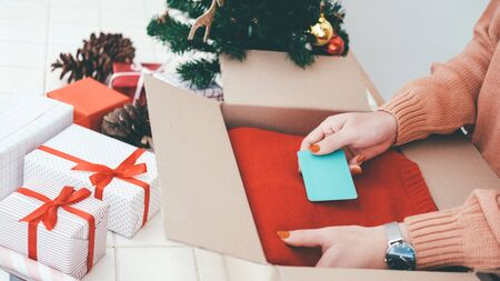 Woman prepare christmas and new year gift and put the card into box. Christmas and New year and Birthday concept. Imagens