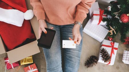 Young woman holding credit card and doing shopping online. New year, Christmas gift shopping. Imagens