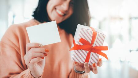 Happy smiling woman holding white blank card and gift box. Blank card for customize text. Фото со стока - 137270001