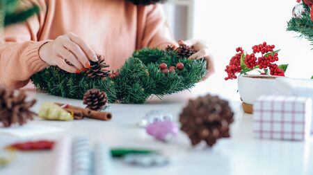 Christmas decoration. Woman hands decorating the Christmas tree and Christmas wreath.