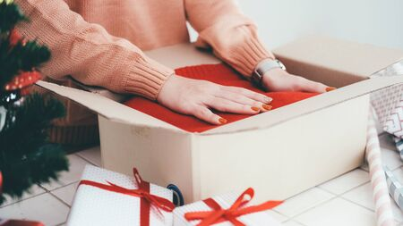 Woman preparing presents for Christmas and New Year. Holiday concept.