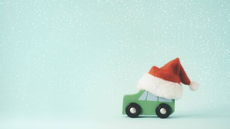 Christmas or New year minimal concept copy space background. The wooden toy car and Santa Claus hat on snow and mint color background.