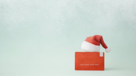 Christmas shopping idea concept background. Credit card and Santa Claus hat on bokeh background. Zdjęcie Seryjne