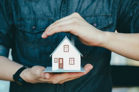 Business man hand hold the house model saving small house. House insurance. Imagens