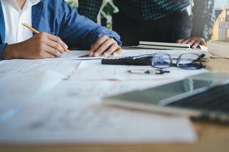 職場でパートナーやエンジニアリングツールを使用して作業する建築プロジェクトのエンジニアミーティングのイメージ。