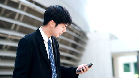 Young businessman using mobilephone app texting outside of office with skyscrapers buildings in background. Young man holding smartphone for business work.