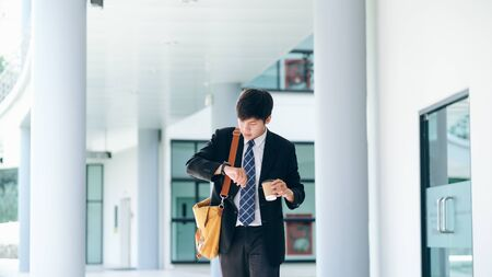 Businessman running late for work. Young businessman worried looking at his wrist watch. Фото со стока - 137840062