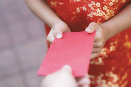 Chinese Lunar New Year celebrations. People giving red envelope (ang pao) to child. Фото со стока