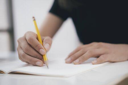 Chiuda sulle mani con la scrittura della penna sul taccuino. Concetto di educazione.