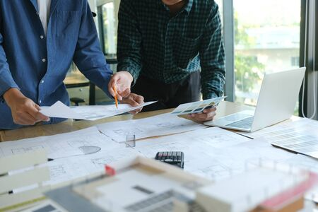 Image of engineer meeting for architectural project working with partner and engineering tools on workplace.