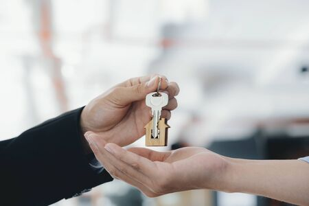 Real estate agent holding key with house shaped keychain. Real estate, buy or sale or moving home or renting property. Mortgage and business concept.