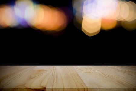 Empty wood table over bokeh at night for product display montage.
