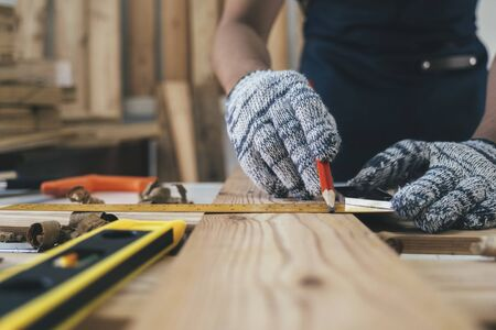 DIY woodworking and furniture making and craftsmanship and handwork concept. Carpenter working on woodworking machines in carpentry shop. Young man working as carpenter and taking wood stock. Фото со стока
