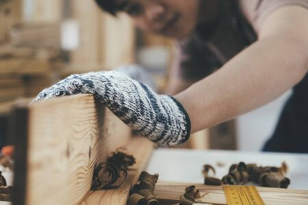 DIY woodworking and furniture making and craftsmanship and handwork concept. Carpenter working on woodworking machines in carpentry shop. Young man working as carpenter and taking wood stock.