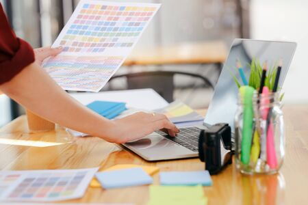 Graphic designer working with color samples for selection. Graphic designer at work. Color swatch samples. Young photographer and graphic designer at work in office. Stock Photo