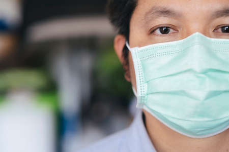 Closeup man wearing hygienic mask to prevent infection, airborne respiratory illness such as flu, 2019-nCoV.  Protection against contagious disease, coronavirus.