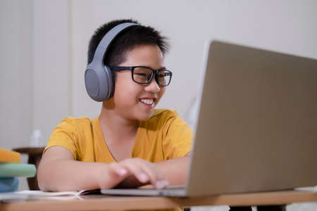 Cheerfully boy excited using computer online learning schoolwork. Asian boy enjoy self study with e-learning at home. Online education and self study and homeschooling concept.