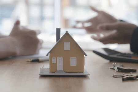 Close up house model on blur background of real estate agent and customer. Business and finance of buy sell and rent real estate concept.
