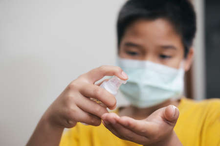 COVID-19, Close up boy using bottle of antibacterial wash hand sanitizer gel dispenser, against Novel coronavirus (2019-nCoV) at home.  Home isolation and Healthcare concept. Stock Photo