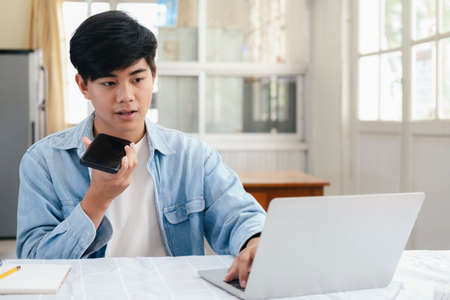 Young man talking on the phone with handfree and using laptop working and meeting online at home.